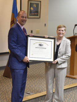 General Irwin and Acting Director Craig Brown holding up a framed certificate